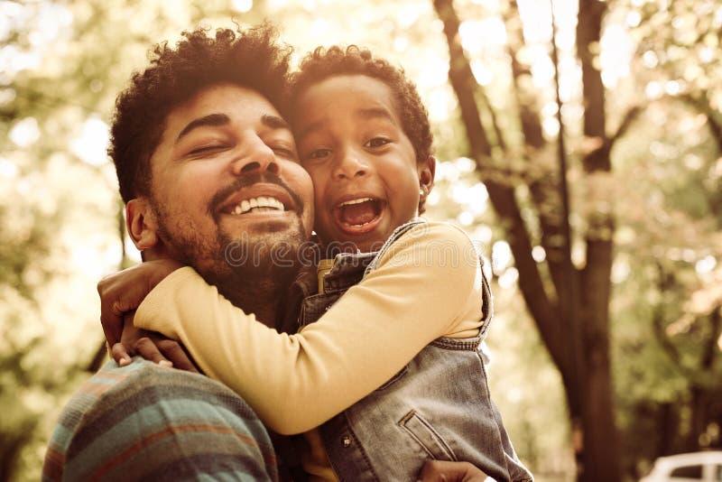 Padre afroamericano que abraza a la pequeña hija en parque fotos de archivo