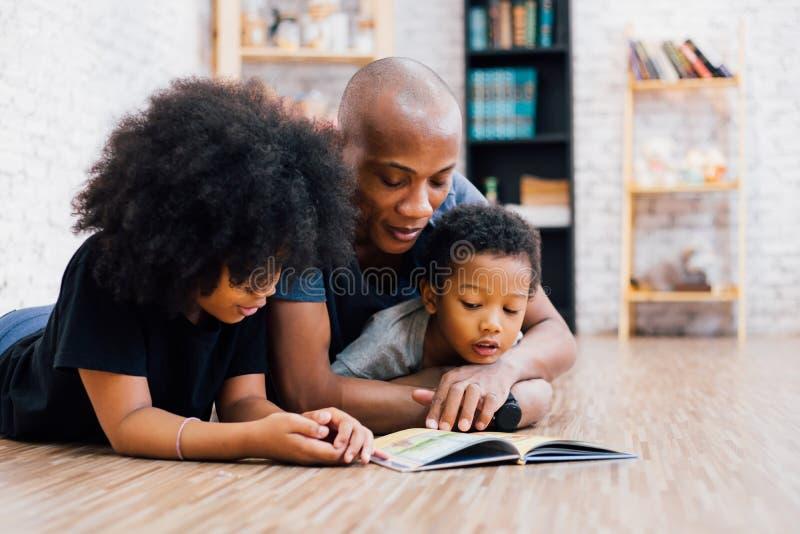 Padre afroamericano que lee una historia de la fábula del cuento de hadas para el niño foto de archivo libre de regalías