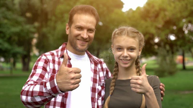 Padre alegre e hija adolescente que sonríen en la cámara, mostrando los pulgares para arriba imágenes de archivo libres de regalías