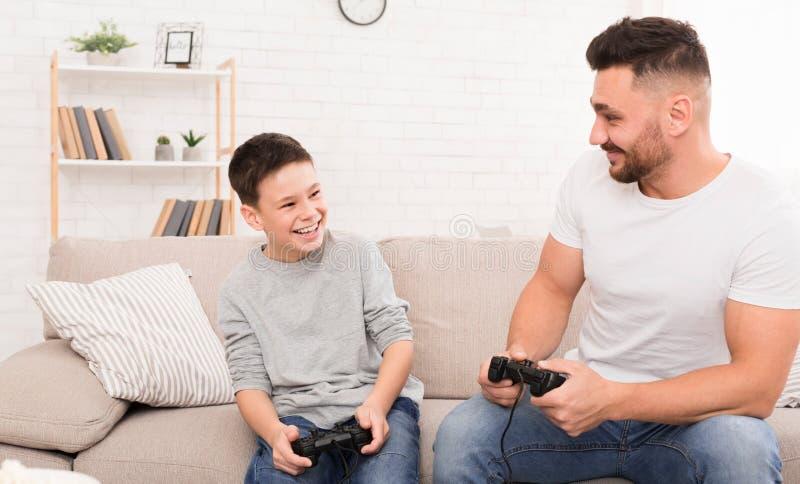 Padre allegro e figlio che giocano video gioco a casa fotografia stock libera da diritti
