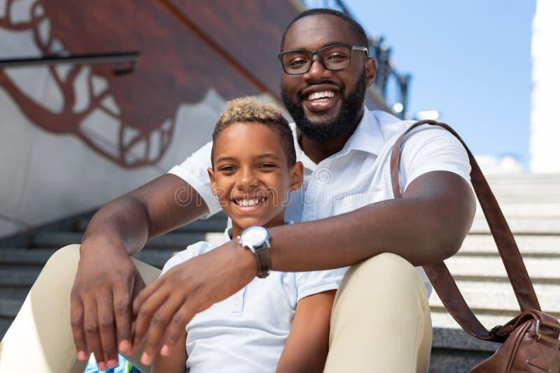 Padre allegro e figlio positivi che godono del loro giorno immagini stock libere da diritti