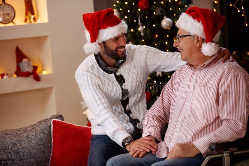 Padre anziano con la sua festa sorridente di Natale di spesa del figlio fotografia stock libera da diritti