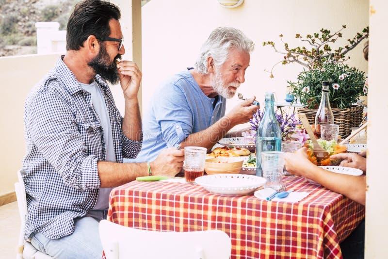 Padre anziano e figlio adulto che pranzano insieme a casa in terrazza esterna diverendosi con amore e amicizia - festivo e fotografia stock