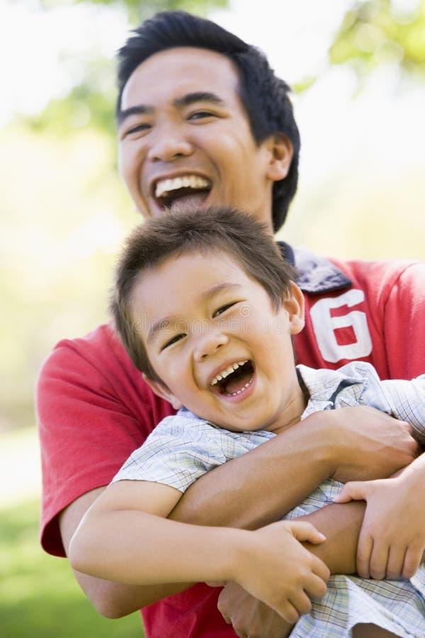 Padre asiático e hijo que se divierten en parque