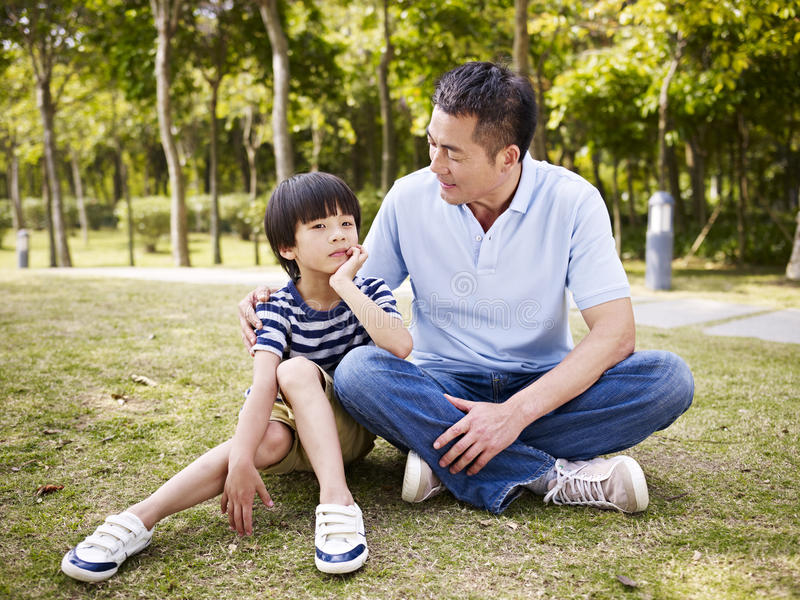 Padre asiático e hijo que tienen una conversación fotos de archivo