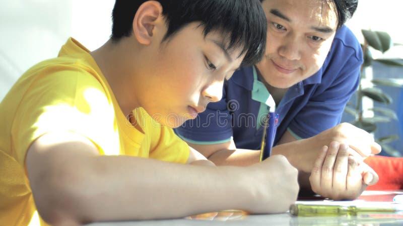 Padre asiático que ayuda a su hijo que hace la preparación en la tabla blanca fotos de archivo