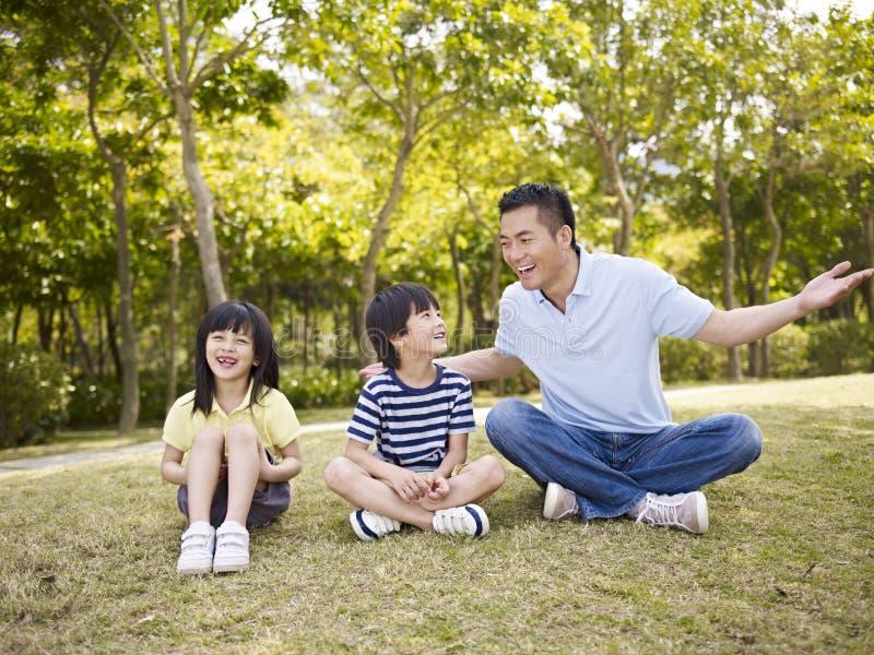 Padre asiático y niños que hablan en parque fotografía de archivo libre de regalías