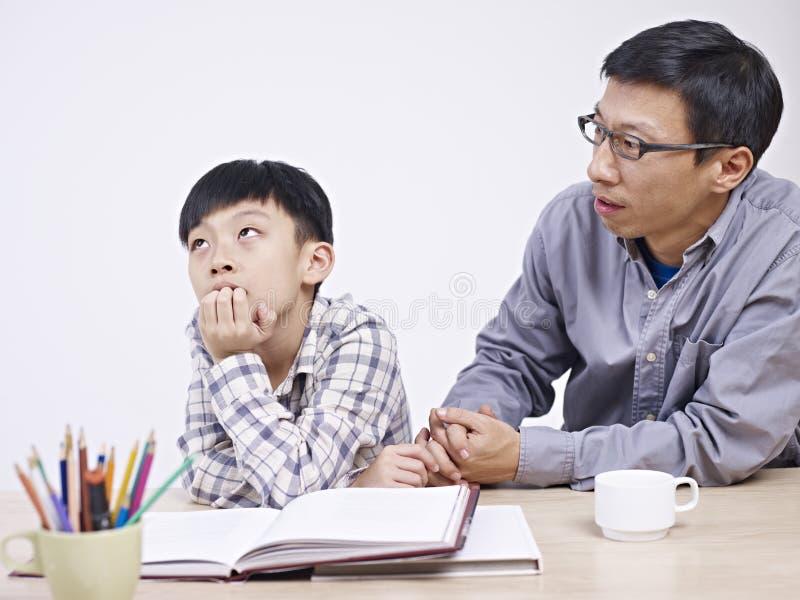 Padre asiatico e figlio che hanno una conversazione seria fotografie stock libere da diritti