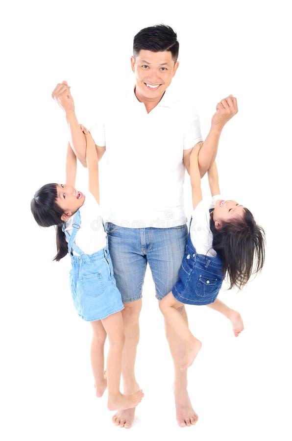 Padre asiatico felice che gioca con le sue figlie immagine stock