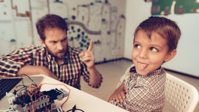 Padre barbudo Help Funny Son con el robot en casa imagen de archivo