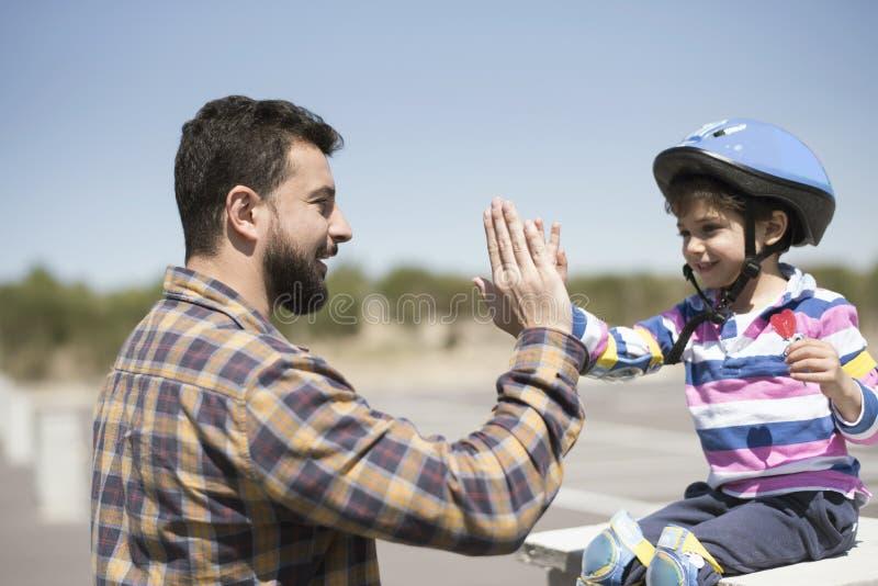 Padre barbudo hola cinco con su pequeño hijo después de montar la bici imágenes de archivo libres de regalías