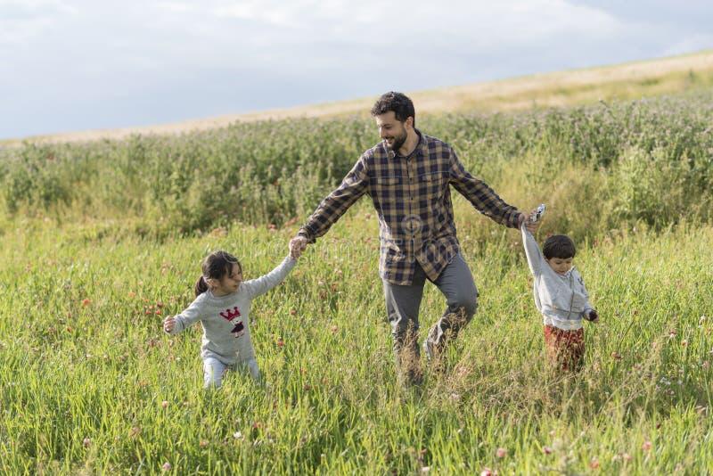 Padre barbudo que camina con su hija e hijo en día de primavera fotografía de archivo libre de regalías
