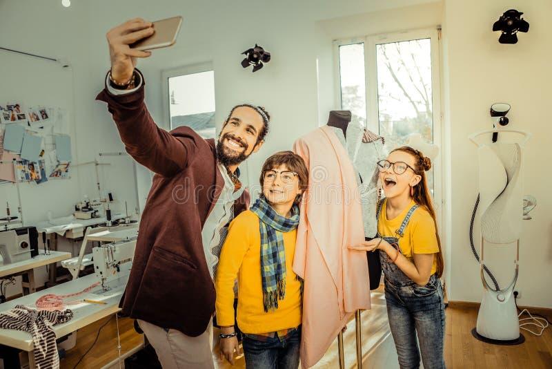Padre barbuto che fa selfie con i suoi bambini amorosi svegli fotografia stock libera da diritti