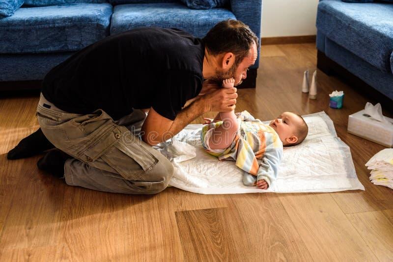 Padre cambiando el pañal sucio de su hija en el piso del salón imagenes de archivo