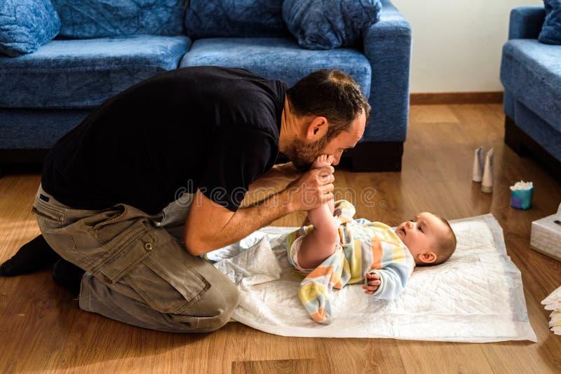 Padre cambiando el pañal sucio de su hija en el piso del salón imágenes de archivo libres de regalías