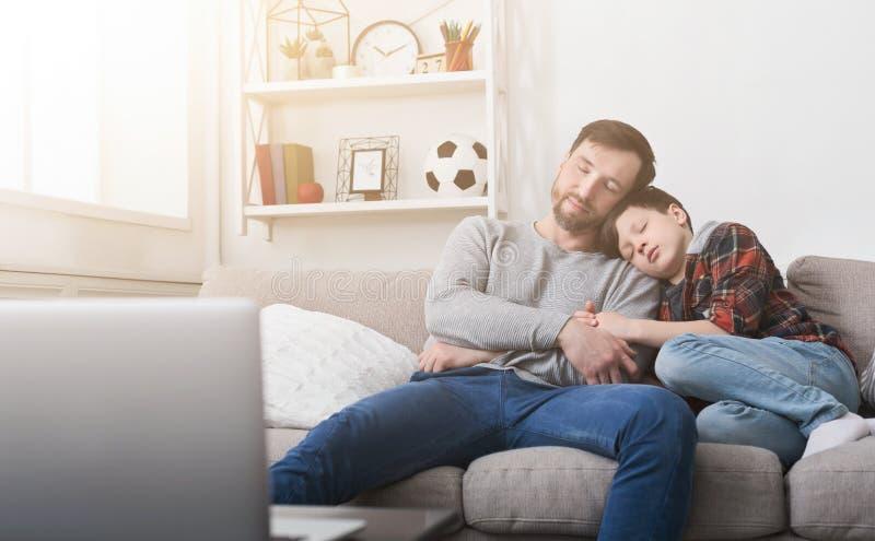 Padre cansado e hijo que duermen en el sofá en casa imágenes de archivo libres de regalías