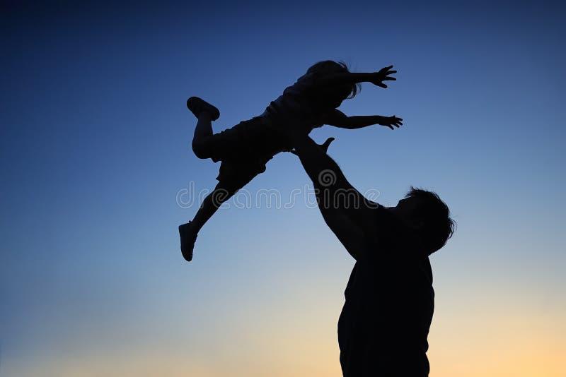 Padre cariñoso y su pequeño hijo que tienen fan junto al aire libre Familia como silueta en puesta del sol foto de archivo libre de regalías