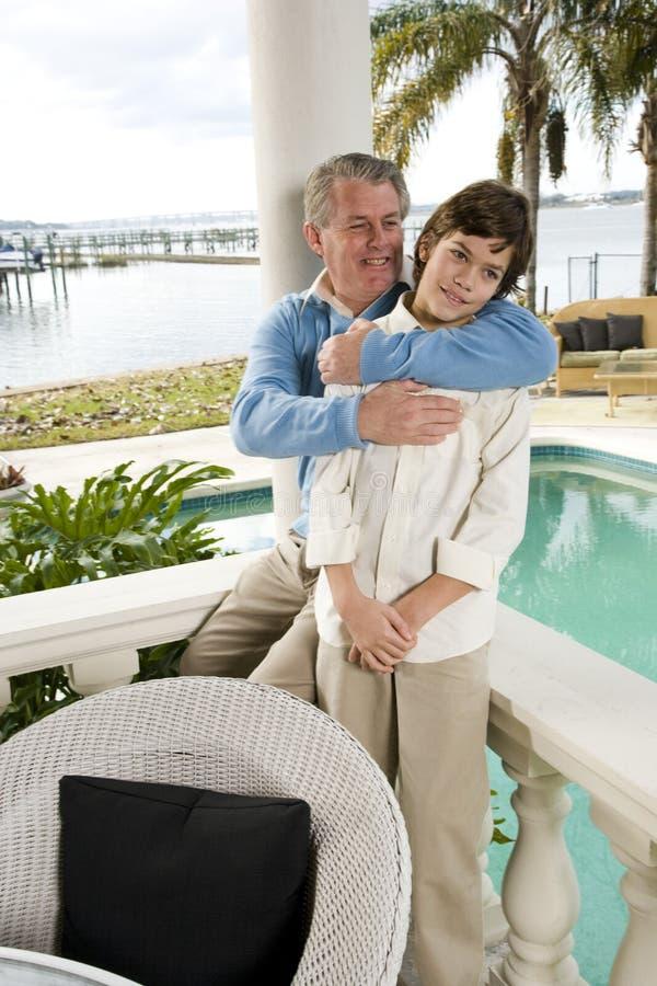 Padre che abbraccia il figlio della Tween fotografia stock