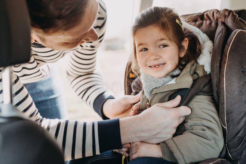 Padre che fissa sua figlia del bambino inarcata nella sua sede di automobile del bambino fotografia stock