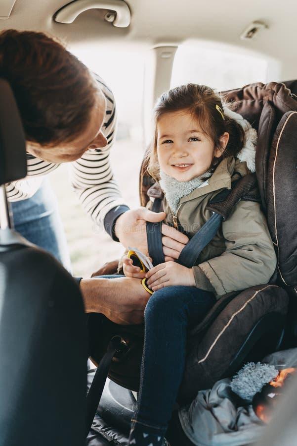 Padre che fissa sua figlia del bambino inarcata nella sua sede di automobile del bambino fotografia stock libera da diritti