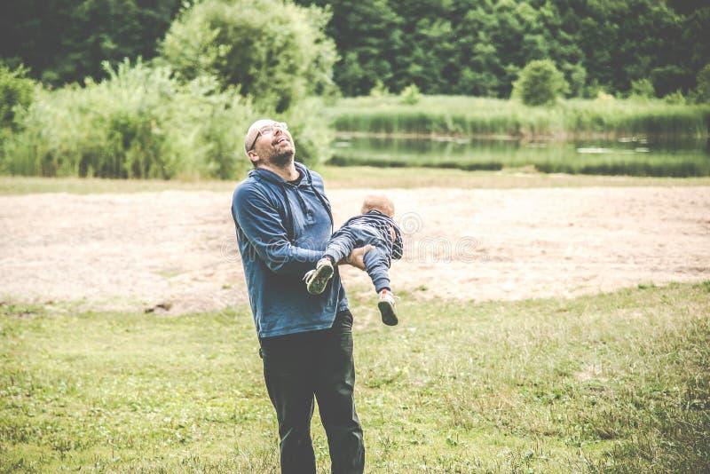 padre che gioca con il suo bambino all'aperto, volo fotografia stock