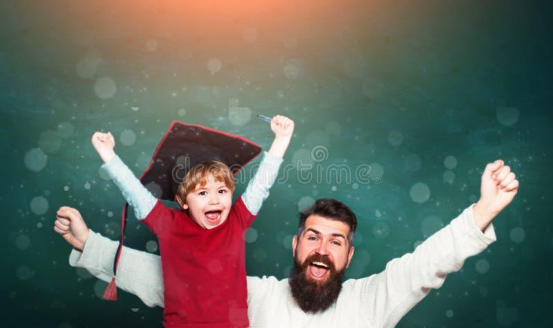 Padre che insegna a suo figlio in aula alla scuola Due generazioni Giovane ragazzo che fa il suo compito della scuola con suo pad immagine stock libera da diritti
