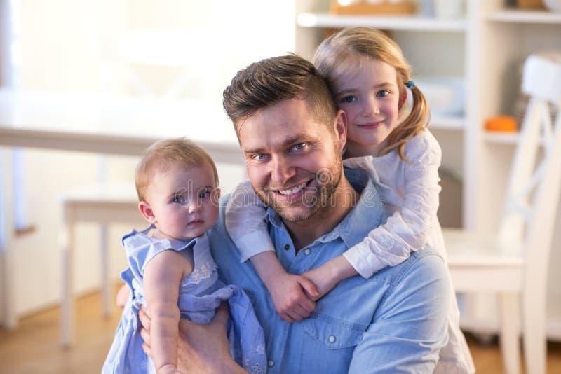Padre che posa con le sue figlie immagini stock