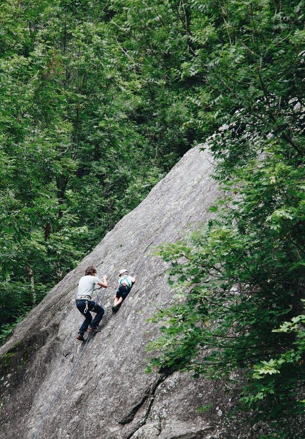 Padre che prepara la sua canzone alla scalata - bambino di arrampicata che rende papà fiero fotografia stock