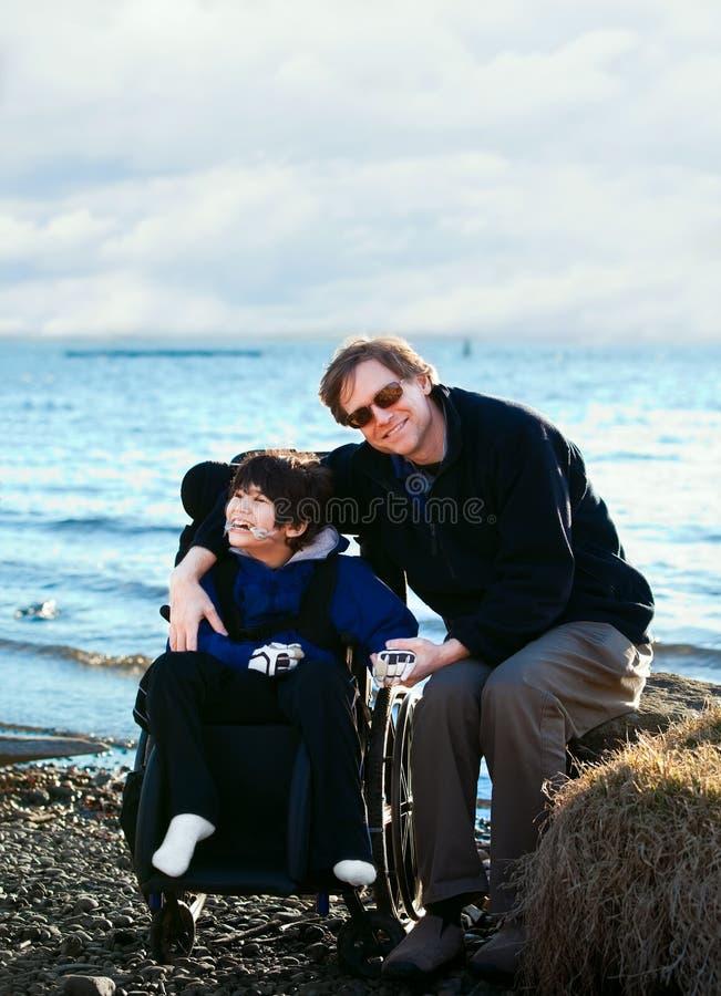 Padre che si siede con il figlio disabile lungo la riva del lago fotografia stock