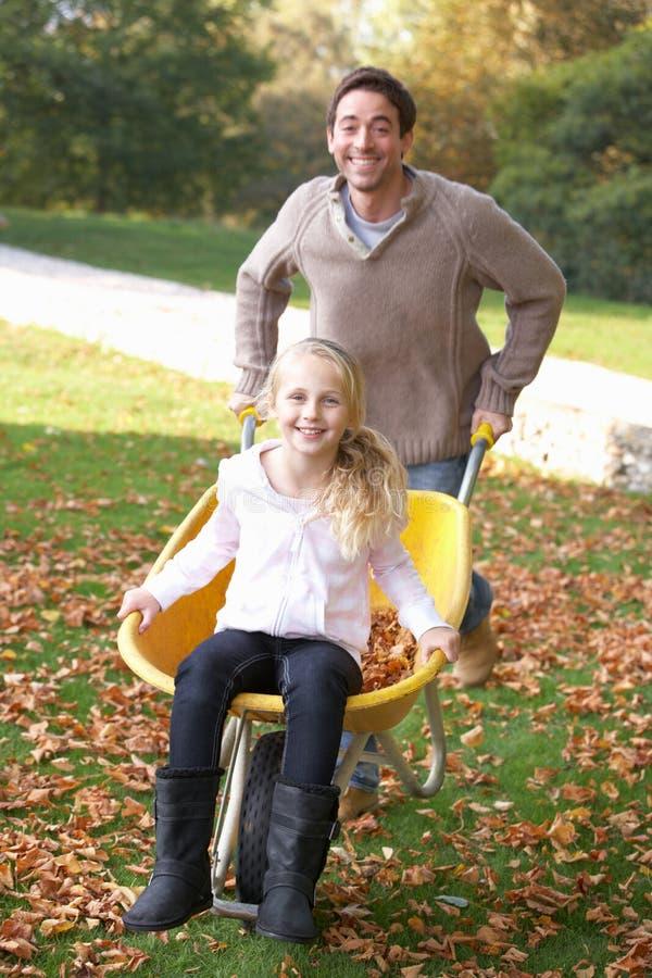 Padre che spinge bambino tramite i fogli di autunno fotografie stock libere da diritti