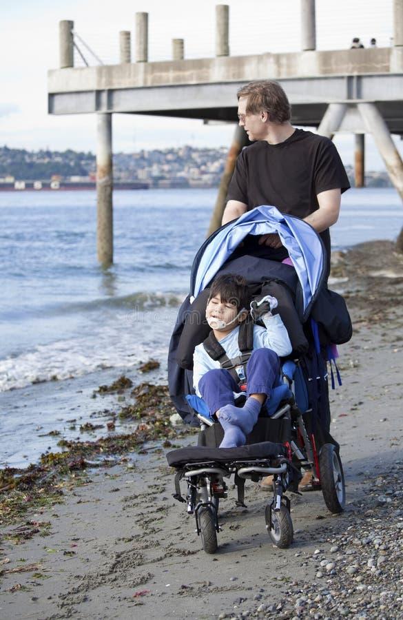 Padre che spinge figlio invalido sulla spiaggia immagini stock libere da diritti