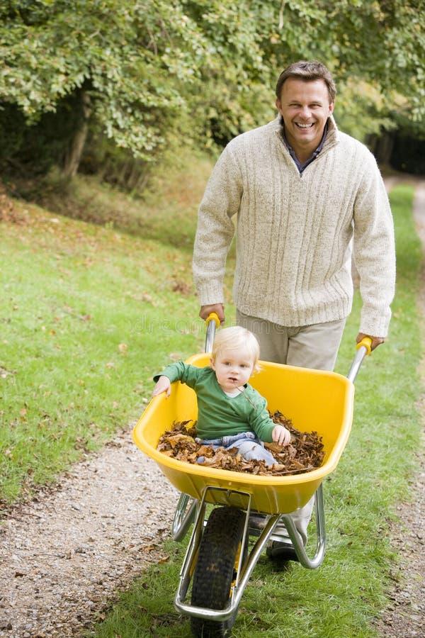 Padre che spinge giovane figlio in carriola fotografia stock