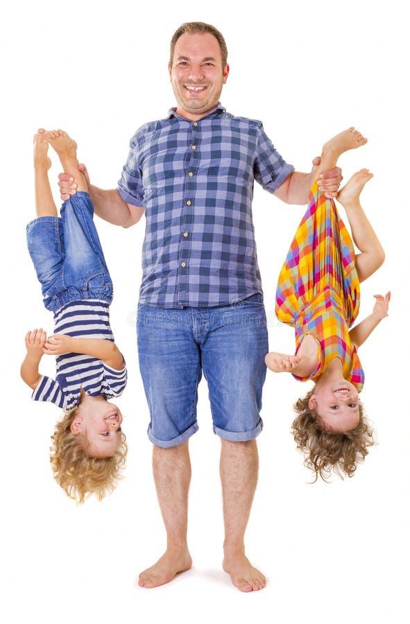 Padre che tiene i suoi bambini sorridenti sottosopra immagini stock