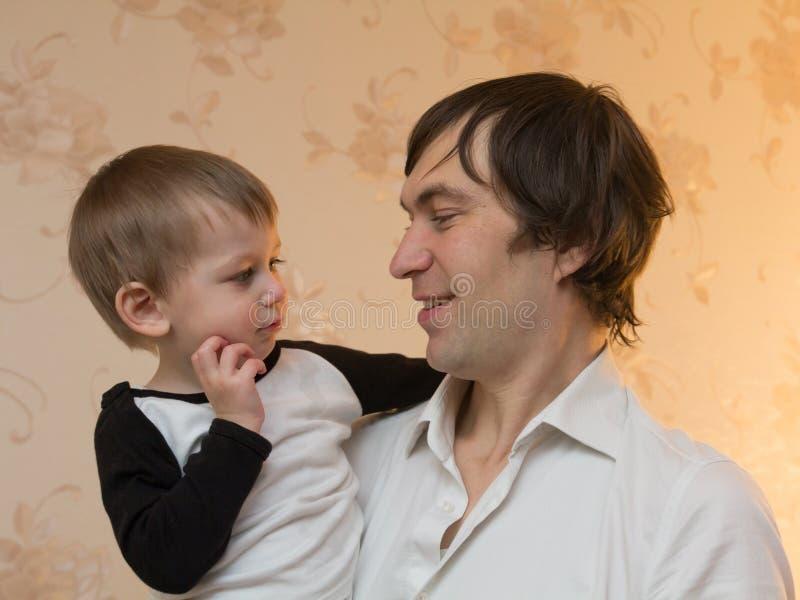 Padre che tiene suo figlio nel suo armi fotografie stock