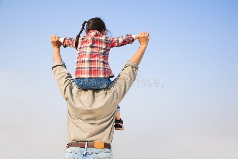 Padre che trasporta la sua figlia sulle spalle immagini stock