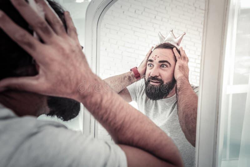Padre che vede il suo fronte dipinto nello specchio prank fotografie stock