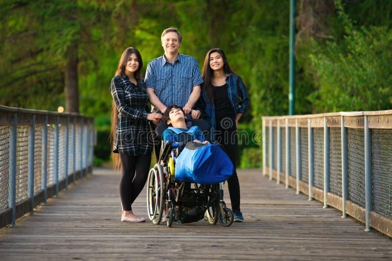 Padre com crianças biraciais na ponte de madeira, necessidades especiais foto de stock