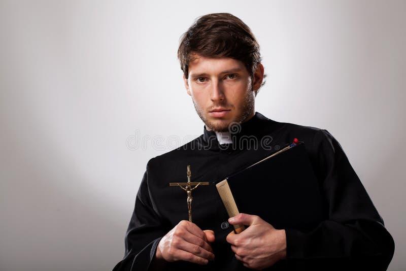 Padre com cruz e Bíblia Sagrada fotografia de stock royalty free