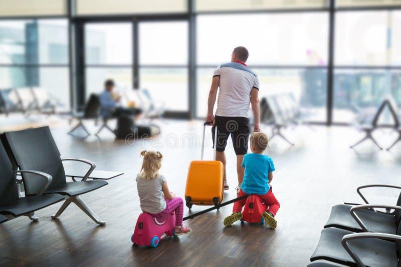 Padre con dos hijos en la terminal del aeropuerto vuelan juntos de vacaciones fotos de archivo libres de regalías