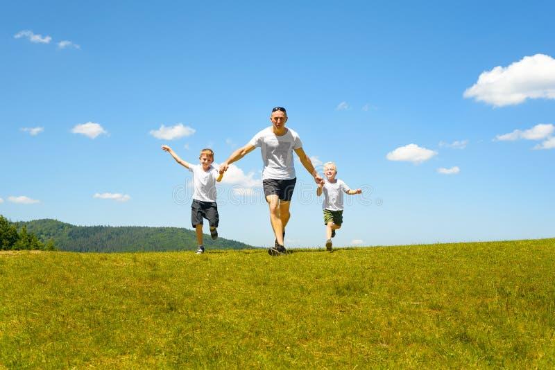 Padre con dos niños jovenes que corren de común acuerdo en el campo verde en un fondo del cielo azul y de nubes Paternidad y fotografía de archivo libre de regalías