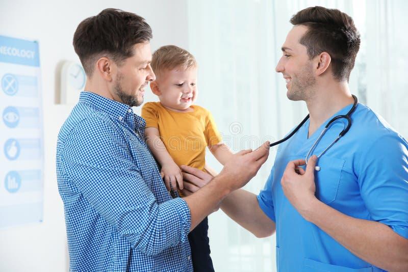 Padre con el doctor que visita del niño imagen de archivo libre de regalías