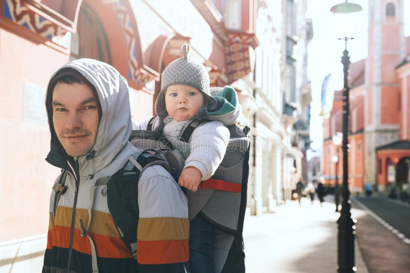 Padre con el hijo del niño en mochila del portador en el viejo centro de Ljubl imagenes de archivo