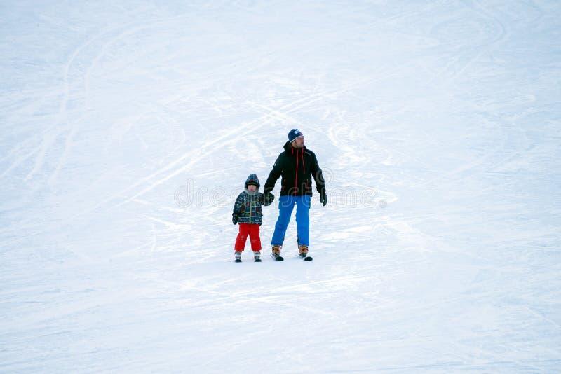Padre con el hijo ir a esquiar del lado de la montaña imágenes de archivo libres de regalías