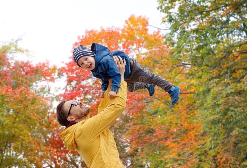 Padre con el hijo que juega y que se divierte en otoño foto de archivo