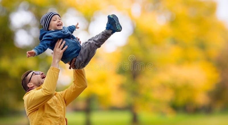 Padre con el hijo que juega y que se divierte en otoño fotos de archivo