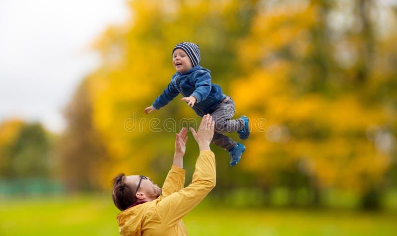 Padre con el hijo que juega y que se divierte en otoño imagenes de archivo