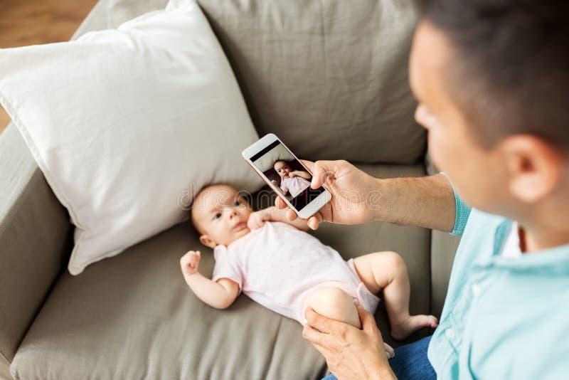 Padre con el smartphone que toma al bebé de la imagen en casa imagenes de archivo