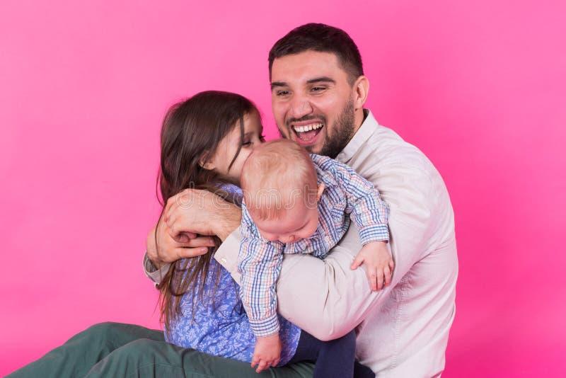 Padre con i bambini divertendosi sul fondo rosa immagini stock libere da diritti