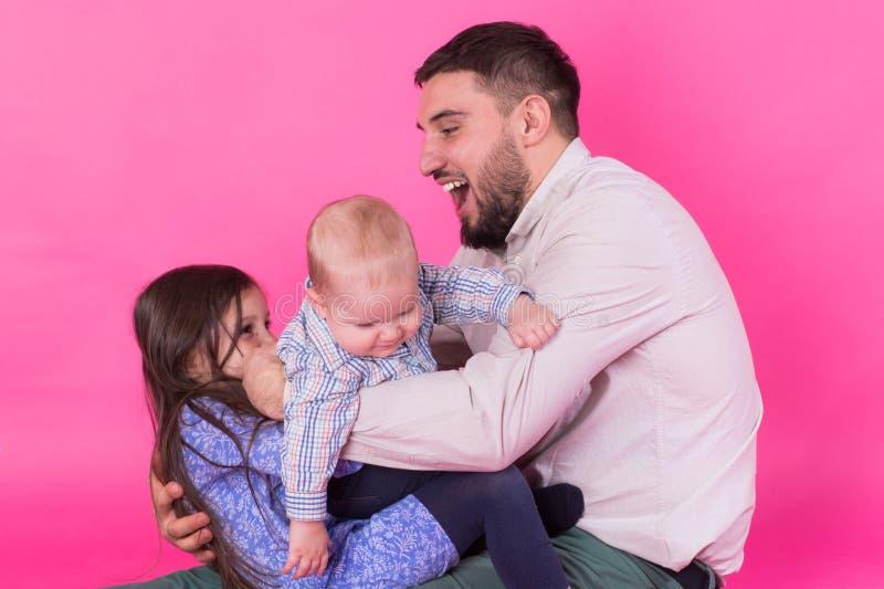Padre con i bambini divertendosi sul fondo rosa fotografia stock