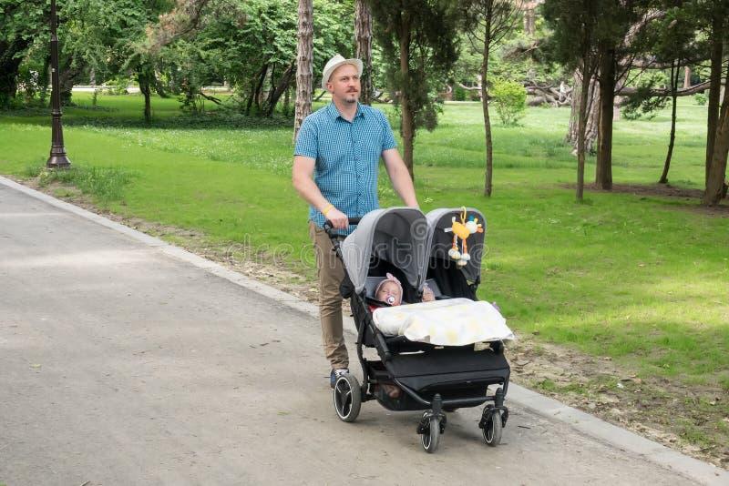Padre con i bambini in doppio passeggiatore in un parco Uomo che spinge i gemelli passeggiatore, carrozzina immagini stock libere da diritti